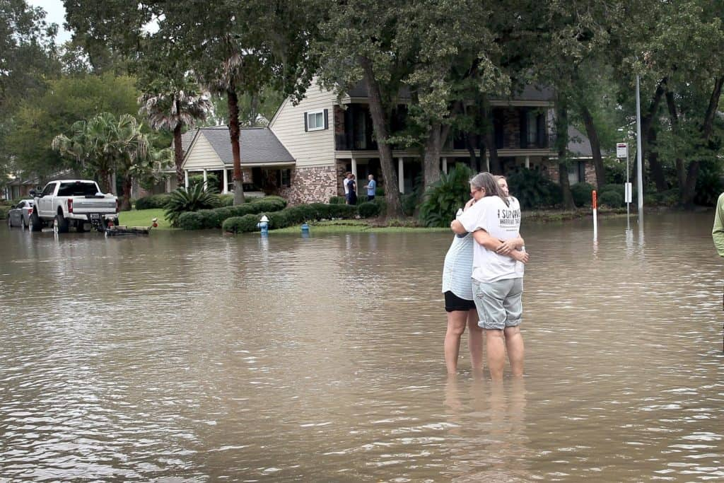 Friends reunite in the middle of a flooded intersection as water continues to rise in their neighborhood following Hurricane HarveyScott Olson / Getty Images