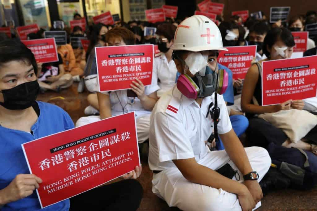 Health care staff stage a demonstration at Queen Elizabeth Hospital on Tuesday to protest against alleged use of force by police on anti-government protesters. Photo: Nora Tam