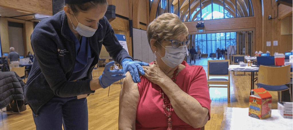 A woman receives her first vaccine shot at Duke Health.
